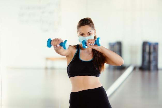 Mujer joven usar máscara y hacer ejercicios con pesas