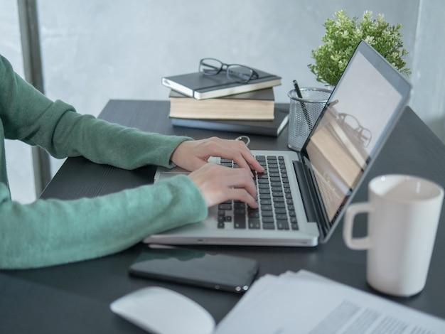 Mujer joven utiliza una computadora portátil en el escritorio negro en casa.