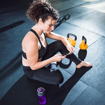Mujer joven, utilizar, teléfono celular, en, gimnasio