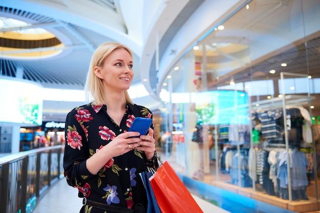 Mujer joven, utilizar, teléfono móvil, en, centro comercial