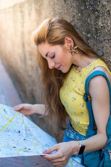 Mujer joven de vacaciones leyendo un mapa de turismo durante sus vacaciones de verano en españa
