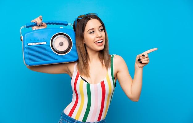 Mujer joven en vacaciones de verano sobre azul con una radio