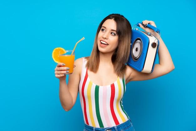 Mujer joven en vacaciones de verano sobre fondo azul con cóctel