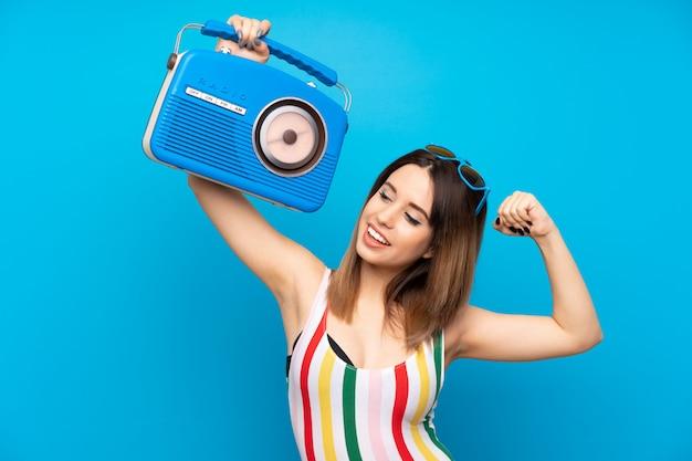 Mujer joven en vacaciones de verano sobre la pared azul con una radio