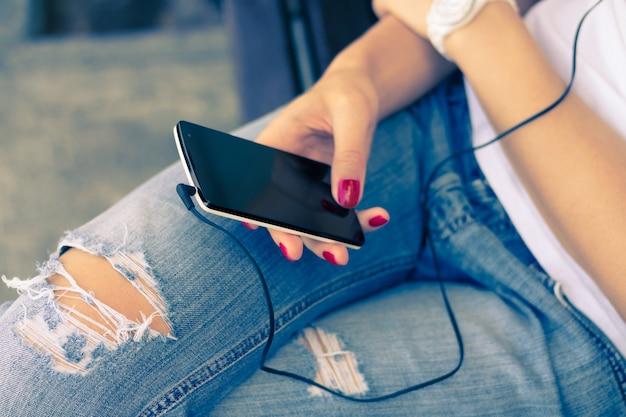 Mujer joven en vaqueros sentados en el banco y conecta los auriculares a su teléfono móvil