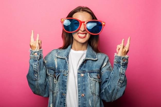 Mujer joven en vasos enormes mostrando gesto de bocina rockero