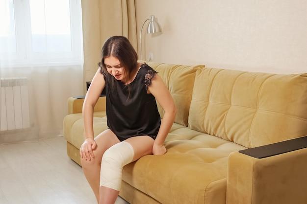 Mujer joven con vendaje en la rodilla con esfuerzo tratando de levantarse del sofá.