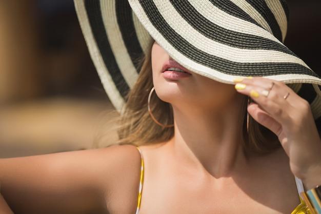 Mujer joven verano retrato de cerca. dama del sombrero. ocio femenino. chica cubriéndose la cara con sombrero despojado