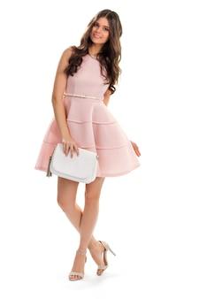 Mujer joven vestida de color salmón. la chica delgada está sonriendo amablemente. vestido sin mangas con pequeño cinturón. modelo con ropa de diseñador.