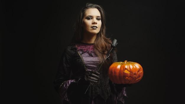 Mujer joven vestida como una bruja para halloween sosteniendo una calabaza aterradora sobre fondo negro