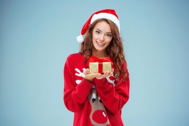 Mujer joven vestida con gorro de papá noel con un regalo de navidad