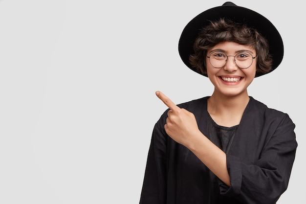 Mujer joven vestida con ropa negra y anteojos redondos