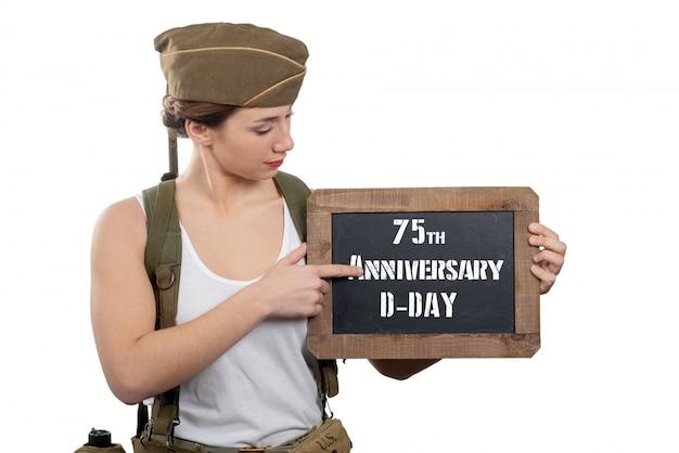 Mujer joven vestida con el uniforme militar americano ww2 que muestra la pizarra con el aniversario del día d