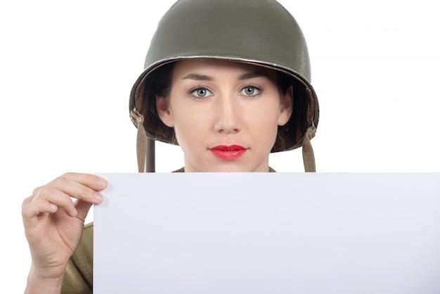 Mujer joven vestida con el uniforme militar de ee. uu. ww2 con demostración de casco