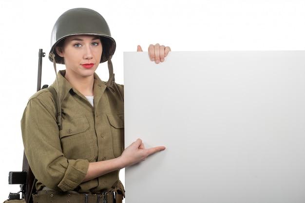 Una mujer joven vestida con uniforme militar estadounidense ww2 que muestra un letrero vacío en blanco