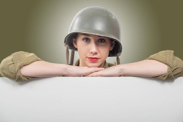 Mujer joven vestida con uniforme de wwii nos militares con casco mostrando vacío letrero en blanco