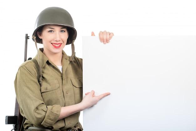 Mujer joven vestida en ww2 militar nos uniforme con casco showi