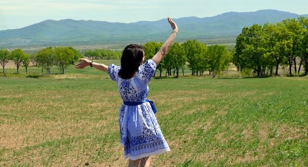 Mujer joven en vestido agitando su mano a la naturaleza