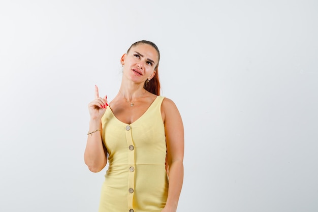 Mujer joven en vestido amarillo apuntando hacia arriba y mirando pensativo, vista frontal.