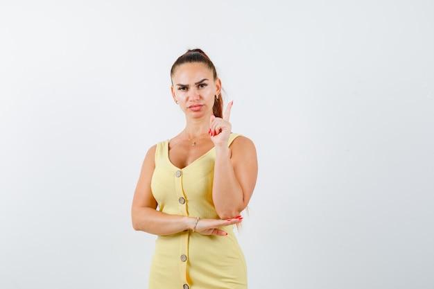 Mujer joven en vestido amarillo apuntando hacia arriba y mirando serio, vista frontal.