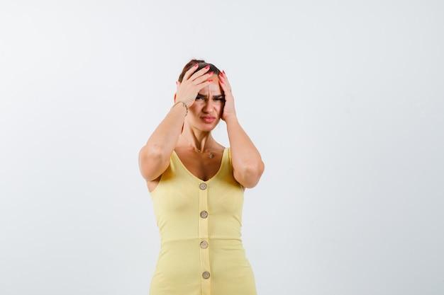 Mujer joven en vestido amarillo cogidos de la mano en la cabeza y mirando triste, vista frontal.