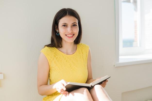 Mujer joven con vestido amarillo leyendo un libro en el interior