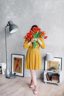 La mujer joven en un vestido amarillo oculta su cara detrás de las flores. chica con gran ramo de tulipán rojo quedarse en casa. retrato de moda en el elegante interior.