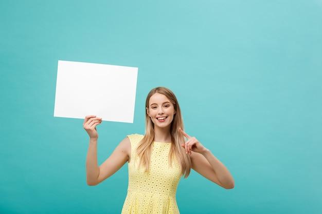 Mujer joven en vestido amarillo que señala el dedo en el tablero blanco en blanco lateral.