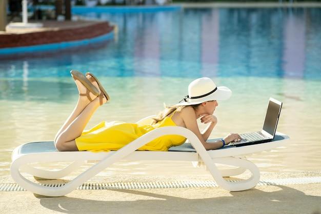 Mujer joven en vestido amarillo está sentado en la silla de playa trabajando en equipo portátil conectado a internet inalámbrico escribiendo texto en las teclas en el resort de verano.