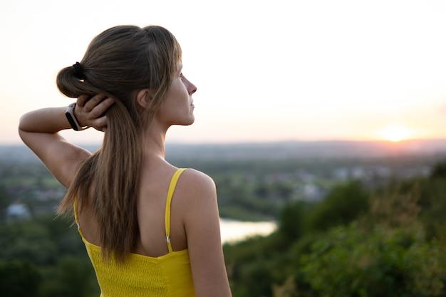 Mujer joven en vestido amarillo de verano de pie en el prado verde disfrutando de la vista del atardecer.