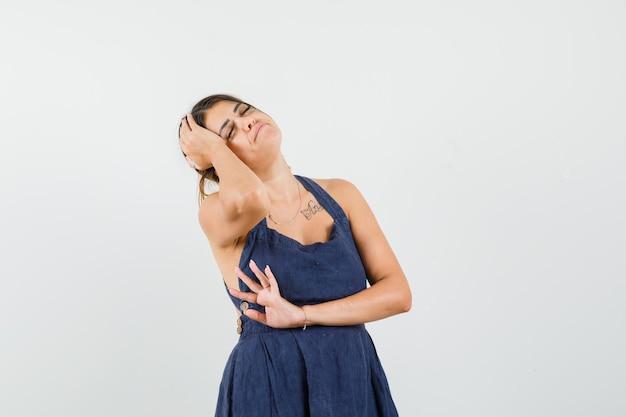 Mujer joven en vestido azul oscuro que sufre de dolor de cabeza y parece cansado