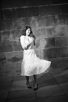 Mujer joven en vestido blanco bailando en la calle