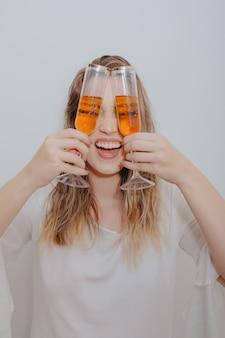 Mujer joven con vestido blanco y con dos copas de vino espumoso en las manos frente a su cara