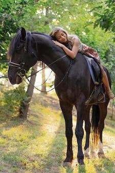 Mujer joven en un vestido colorido brillante montando un caballo negro
