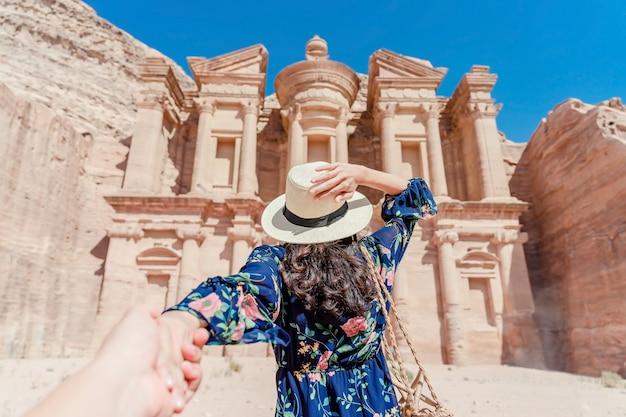Mujer joven en un vestido colorido y un sombrero que sostiene la mano del hombre y lo lleva al monasterio