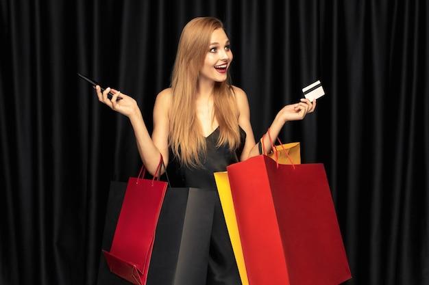 Mujer joven, en, vestido, compras, en, pared negra