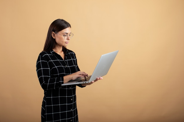 Una mujer joven en un vestido a cuadros se alza sobre un fondo naranja con una computadora portátil