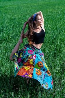 Mujer joven con un vestido floral meditando en el campo de hierba