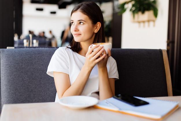 Mujer joven en vestido gris sentado en la mesa de café y escribir en el cuaderno. estudiante aprendiendo en línea.