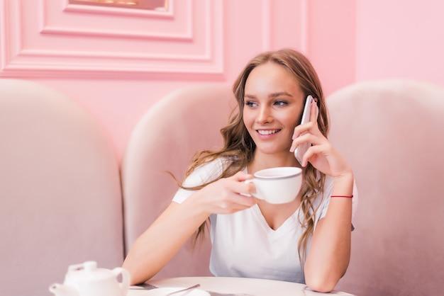 Mujer joven en vestido gris sentado a la mesa en la cafetería, hablando por teléfono celular mientras toma notas en el cuaderno.