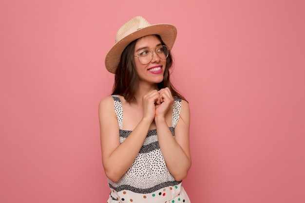 Mujer joven en vestido gris con sombrero y gafas
