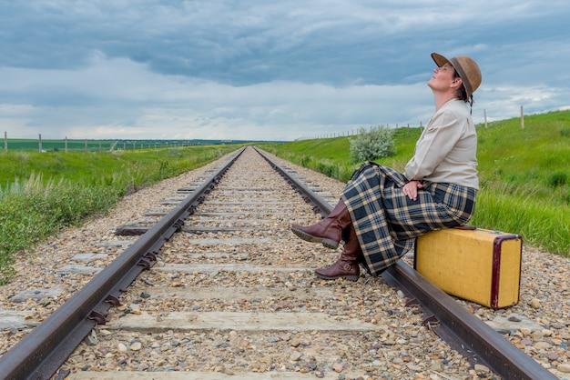 Mujer joven en vestido histórico sentado en una maleta vintage en vía férrea con la cabeza hacia atrás y los ojos cerrados concepto de viaje