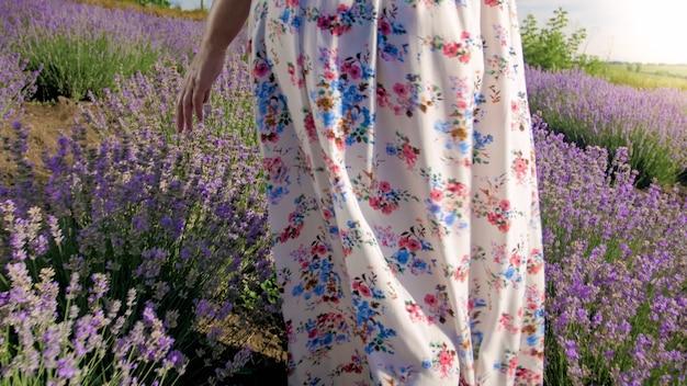 Mujer joven con vestido largo caminando sobre campo de lavanda en la mañana.
