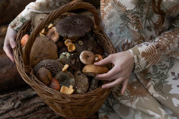 Mujer joven en un vestido de lino recogiendo setas en el bosque
