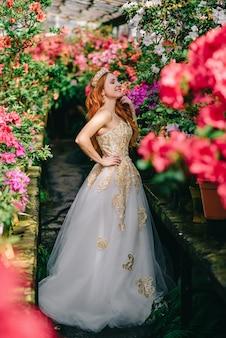Mujer joven en vestido de lujo de pie en el jardín de flores