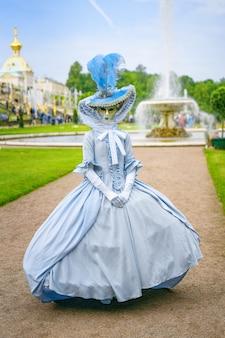 Mujer joven en vestido y máscara veneciana