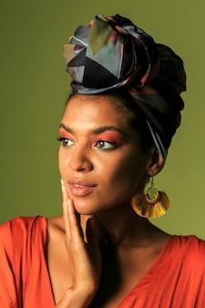 Mujer joven con vestido naranja con turbante y joyería étnica