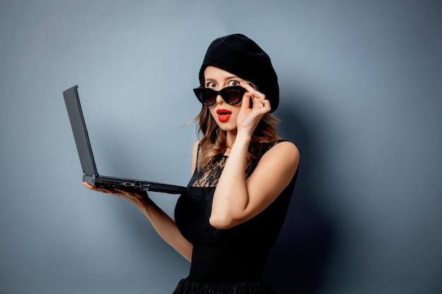 Mujer joven en vestido negro con cuaderno en pared gris