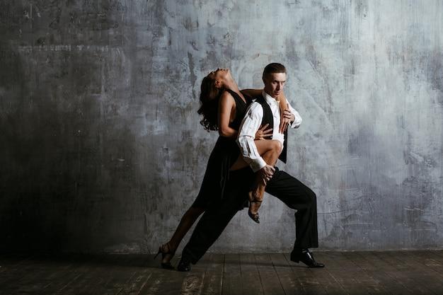 Mujer joven en vestido negro y hombre adulto bailando tango.