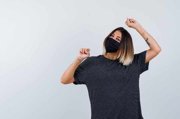 Mujer joven en vestido negro, máscara negra que muestra el gesto del ganador y parece afortunado, vista frontal.